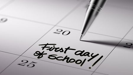 Closeup of a personal agenda setting an important date written with pen. The words First day of school written on a white notebook to remind you an important appointment. Imagens