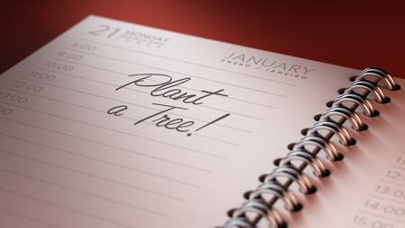 Closeup of a personal calendar setting an important date representing a time schedule. The words Plant a tree written on a white notebook to remind you an important appointment.