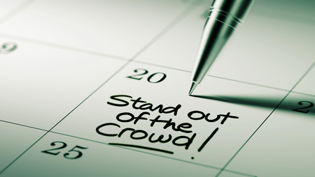 out of date: Closeup of a personal agenda setting an important date written with pen. The words Stand out of the crowd written on a white notebook to remind you an important appointment. Stock Photo