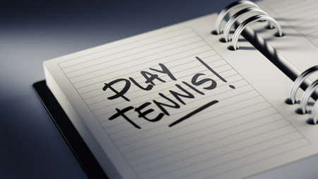 play date: Closeup of a personal agenda setting an important date representing a time schedule. The words Play Tennis written on a white notebook to remind you an important appointment.