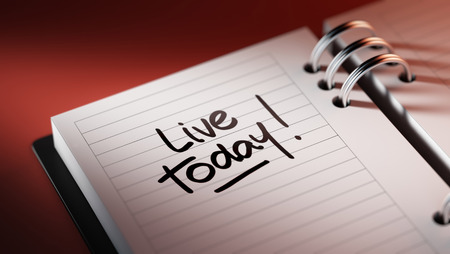 living moment: Closeup of a personal agenda setting an important date representing a time schedule. The words Live today written on a white notebook to remind you an important appointment. Stock Photo