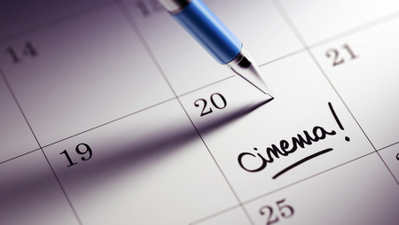 written date: Closeup of a personal agenda setting an important date written with pen. The words Cinema written on a white notebook to remind you an important appointment.