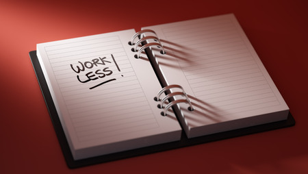 work less: Closeup of a personal agenda setting an important date representing a time schedule. The words Work Less written on a white notebook to remind you an important appointment. Stock Photo