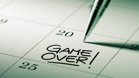 failed plan: Closeup of a personal agenda setting an important date written with pen. The words Game over written on a white notebook to remind you an important appointment. Stock Photo