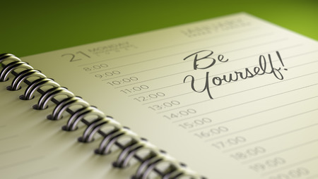 be yourself: Closeup of a personal calendar setting an important date representing a time schedule. The words be yourself written on a white notebook to remind you an important appointment.