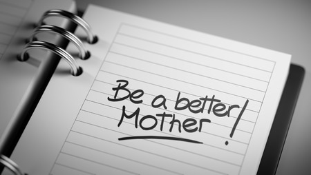 mother to be: Closeup of a personal agenda setting an important date representing a time schedule. The words Be a better mother written on a white notebook to remind you an important appointment.