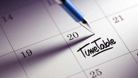 cronologia: Closeup of a personal agenda setting an important date written with pen. The words Timetable written on a white notebook to remind you an important appointment.