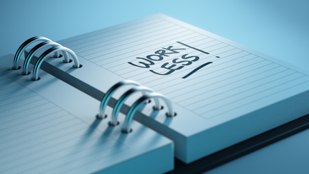 fewer: Closeup of a personal agenda setting an important date representing a time schedule. The words Work Less written on a white notebook to remind you an important appointment. Stock Photo