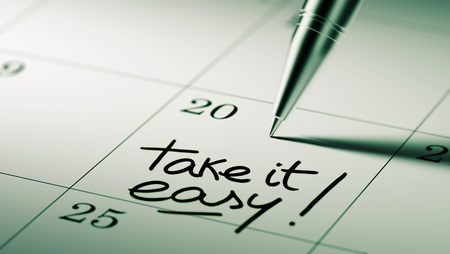 take it easy: Closeup of a personal agenda setting an important date written with pen. The words Take it easy written on a white notebook to remind you an important appointment.
