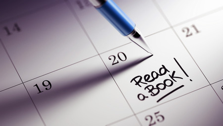 date book: Closeup of a personal agenda setting an important date written with pen. The words Read a book written on a white notebook to remind you an important appointment.