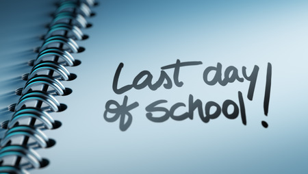 Closeup of a personal calendar setting an important date representing a time schedule. The words Last day of school written on a white notebook to remind you an important appointment.