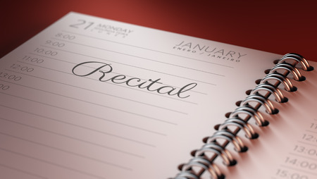 recital: Closeup of a personal calendar setting an important date representing a time schedule. The words Recital written on a white notebook to remind you an important appointment.