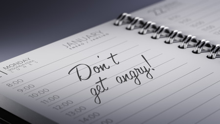 Closeup of a personal calendar setting an important date representing a time schedule. The words Dont get angry written on a white notebook to remind you an important appointment. Stock Photo