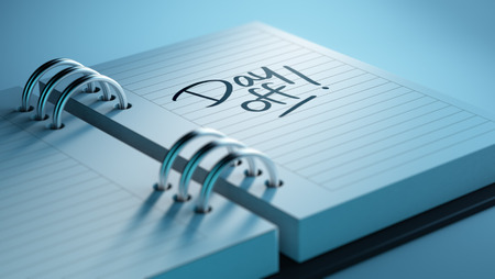 Closeup of a personal agenda setting an important date representing a time schedule. The words Day off written on a white notebook to remind you an important appointment. Stock Photo
