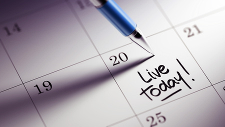 living moment: Closeup of a personal agenda setting an important date written with pen. The words Live today written on a white notebook to remind you an important appointment.