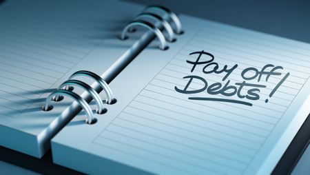pay off: Closeup of a personal agenda setting an important date representing a time schedule. The words Pay off debts written on a white notebook to remind you an important appointment. Stock Photo