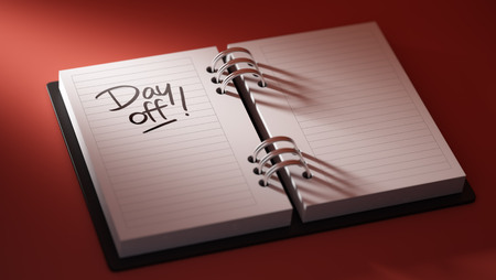 write off: Closeup of a personal agenda setting an important date representing a time schedule. The words Day off written on a white notebook to remind you an important appointment. Stock Photo