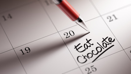 written date: Closeup of a personal agenda setting an important date written with pen. The words Eat Chocolate written on a white notebook to remind you an important appointment.