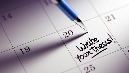 hipótesis: Primer plano de una fijación de una fecha importante por escrito con la pluma agenda personal. Escribir las palabras de su tesis escrita en un cuaderno en blanco para que le recuerde una cita importante.