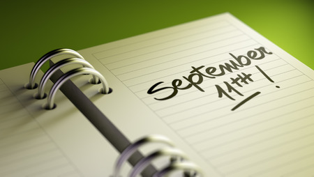 11th: Closeup of a personal agenda setting an important date representing a time schedule. The words September 11th written on a white notebook to remind you an important appointment. Stock Photo