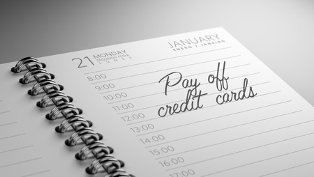 pay off: Closeup of a personal calendar setting an important date representing a time schedule. The words Pay off Credit cards written on a white notebook to remind you an important appointment.