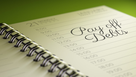 pay off: Closeup of a personal calendar setting an important date representing a time schedule. The words Pay off debts written on a white notebook to remind you an important appointment.