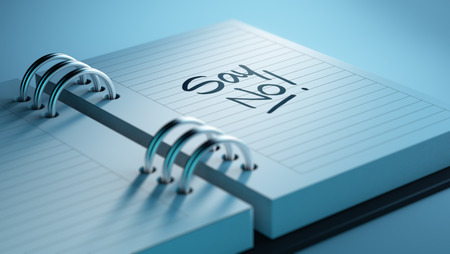 denying: Closeup of a personal agenda setting an important date representing a time schedule. The words Say NO written on a white notebook to remind you an important appointment. Stock Photo