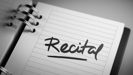 recital: Closeup of a personal agenda setting an important date representing a time schedule. The words Recital written on a white notebook to remind you an important appointment.