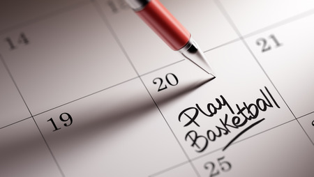 play date: Closeup of a personal agenda setting an important date written with pen. The words Play Basketball written on a white notebook to remind you an important appointment. Stock Photo