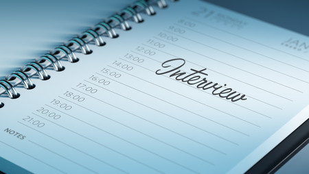 oral communication: Closeup of a personal calendar setting an important date representing a time schedule. The words Interview written on a white notebook to remind you an important appointment.