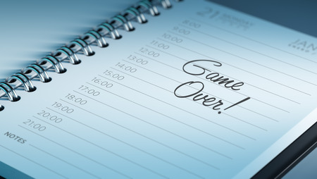 play date: Closeup of a personal calendar setting an important date representing a time schedule. The words Game over written on a white notebook to remind you an important appointment.
