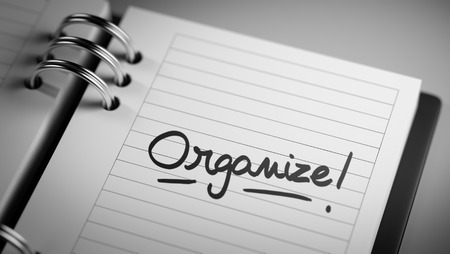 important date: Closeup of a personal agenda setting an important date representing a time schedule. The words Organize written on a white notebook to remind you an important appointment.