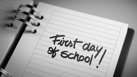 Closeup of a personal agenda setting an important date representing a time schedule. The words First day of school written on a white notebook to remind you an important appointment.