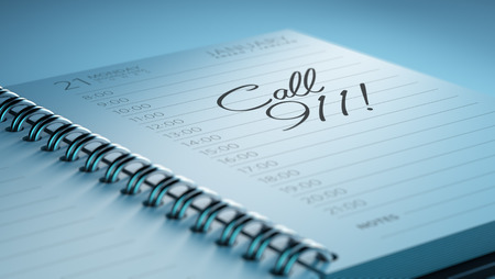 personal call: Closeup of a personal calendar setting an important date representing a time schedule. The words Call 911 written on a white notebook to remind you an important appointment. Stock Photo