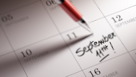 11th: Closeup of a personal agenda setting an important date written with pen. The words September 11th written on a white notebook to remind you an important appointment.