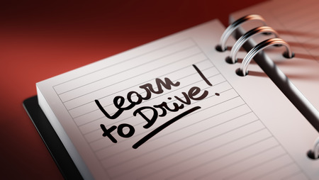 time drive: Closeup of a personal agenda setting an important date representing a time schedule. The words Learn to Drive written on a white notebook to remind you an important appointment. Stock Photo