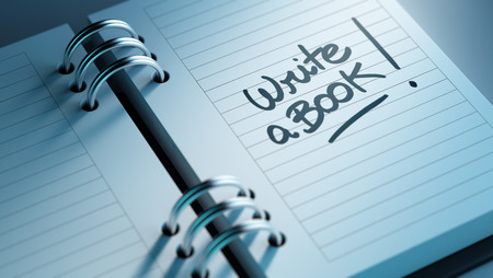 appointment book: Closeup of a personal agenda setting an important date representing a time schedule. The words Write a Book written on a white notebook to remind you an important appointment.