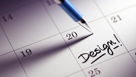 appointment: Closeup of a personal agenda setting an important date written with pen. The words Design written on a white notebook to remind you an important appointment. Stock Photo