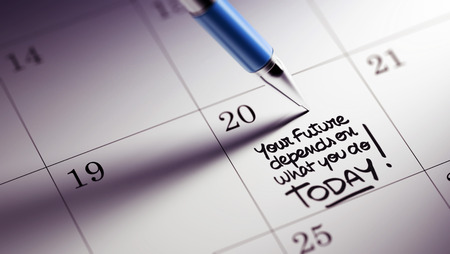 depends: Closeup of a personal agenda setting an important date written with pen. The words Your future depends on what you do today written on a white notebook to remind you an appointment. Stock Photo