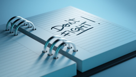 Closeup of a personal agenda setting an important date representing a time schedule. The words Dont Fight written on a white notebook to remind you an important appointment. Stock Photo