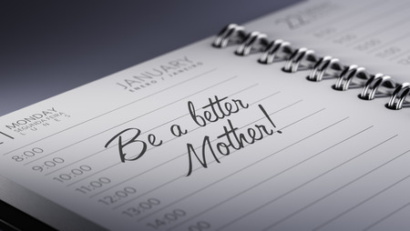 mother to be: Closeup of a personal calendar setting an important date representing a time schedule. The words Be a better mother written on a white notebook to remind you an important appointment.