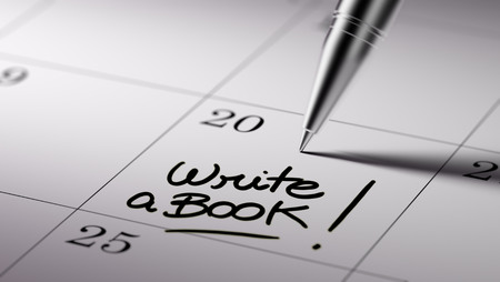 appointment book: Closeup of a personal agenda setting an important date written with pen. The words Write a Book written on a white notebook to remind you an important appointment.