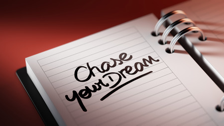 chase: Closeup of a personal agenda setting an important date representing a time schedule. The words Chase your dream written on a white notebook to remind you an important appointment. Stock Photo