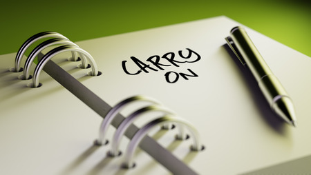 and carry on: Closeup of a personal agenda setting an important date writing with pen. The words Carry on written on a white notebook to remind you an important appointment. Stock Photo