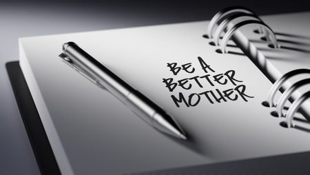 mother to be: Closeup of a personal agenda setting an important date writing with pen. The words Be a better mother written on a white notebook to remind you an important appointment.