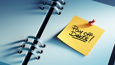 pay off: Closeup Yellow Sticky Note paste it in a notebook setting an appointment. The words Pay off debts written on a white notebook to remind you an important appointment.