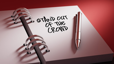 out of date: Closeup of a personal agenda setting an important date writing with pen. The words Stand out of the crowd written on a white notebook to remind you an important appointment. Stock Photo