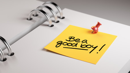 good boy: Closeup Yellow Sticky Note paste it in a notebook setting an appointment. The words Be a good boy written on a white notebook to remind you an important appointment. Stock Photo