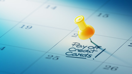 pay off: Concept image of a Calendar with a yellow push pin. Closeup shot of a thumbtack attached. The words Pay off Credit cards written on a white notebook to remind you an important appointment.