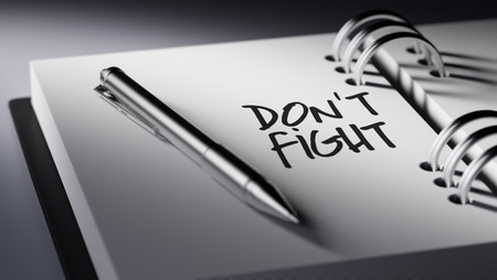 dont: Closeup of a personal agenda setting an important date writing with pen. The words Dont Fight written on a white notebook to remind you an important appointment. Stock Photo